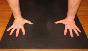 MIDDLE FINGER PERPENDICULAR TO FRONT OF MAT, WRIST ANGLE TURNED IN.