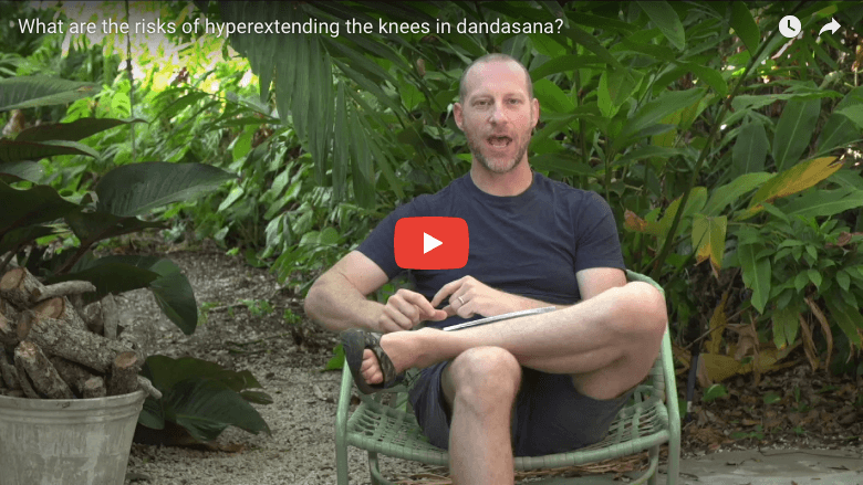What are the risks of hyperextending the knees in dandasana?